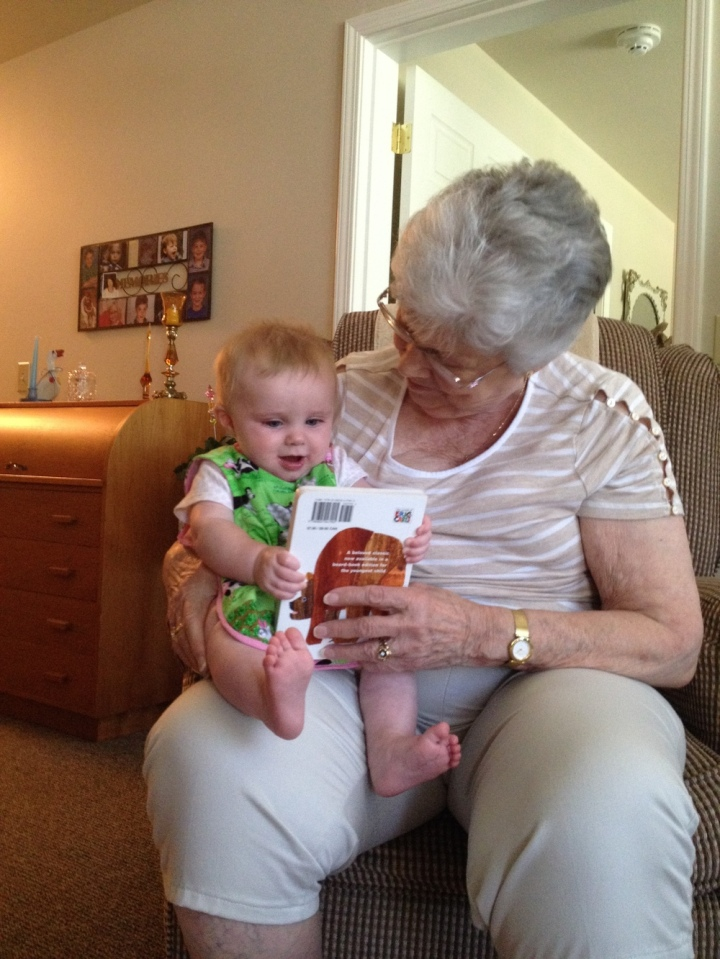 Evie reading a book to Grandma Betty.