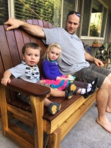 Daddy (AKA Uncle Ryan) and Evie and Edmund sitting on the new glider Adam made for Maryanne for her birthday.